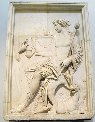 Dionysus - Ancient Roman relief in the Museo Archeologico (Naples) depicting Dionysus holding a thyrsus and receiving a libation, wearing an ivy wreath, and attended by a panther.