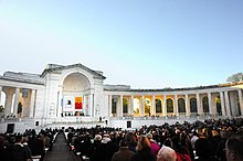 An outdoor auditorium with seated guests lined with neoclassical columns and a closed archway on one side and banners hanging inside the arch.