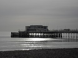 The end of a pier under cloudy skies, illuminated by sunlight reflecting off a calm sea.  There is a small stretch of rocky beach in the foreground.
