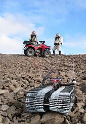 "The DARPA – US Army telerobot ""Solon"" and Crew 3 explore Devo Rock canyon on July 26, 2001."