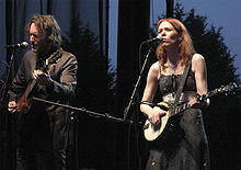 A middle-aged man wearing a dark suit playing guitar while Welch in a black striped dress plays a banjo and sings on stage.