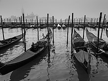 Black-and-white photo on a gray day. In the foreground, four long, narrow boats float side-by-side, left to right, each loosely moored to one of the four tall poles standing in the water (two to each side). Some 30 meters away, in the background, a further row of 15 or 16 gondolas can be seen similarly moored near a railed walkway on the far side. Buildings of Venice appear as distant shadows in the mist.