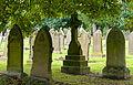 Headstones under trees in Macclesfield Cemetery.jpg