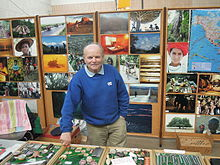 Heinz Stücke stands in front of an array of photos pinned to corkboard. He smiles slightly and leans against one of several glass-covered trays of trinkets on a table before him.