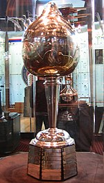 A tall trophy sits inside a glass enclosed display cabinet