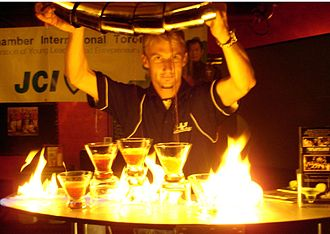Flaming beverage - A man pouring 5 flaming martinis at the same time