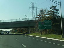 A six-lane freeway at an interchange with an overpass over the road and transmission lines running to the right. A green sign on the right side of the road reads exit 8A County Route 583 south Princeton Pike with an arrow pointing to the upper right