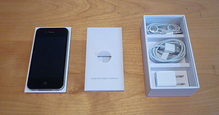 The contents of the box of an iPhone 4. From left to right: iPhone 4 in plastic holder, written documentation, and (top to bottom) headset, USB cable, wall charger. - iPhone