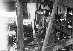 A man in military uniform standing under a wooden structure that has icicles hanging off it