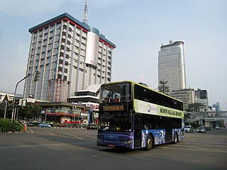 Jakarta doubledecker tourists bus passing in front of Sarinah Thamrin building, Central Jakarta
