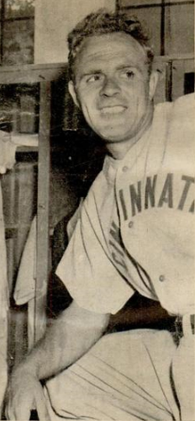 "A man wearing a baseball uniform with ""Cincinnati"" written across the chest stands leaning on a propped up knee and smiles as he looks to the right."