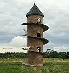 Photograph of a round brick tower with a ramp spiralling from the ground to the roof, with several goats standing on the ramp