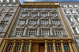 Façade sur rue bicolore, or au premier et dernier niveau, ainsi que sur le pourtour de la façade, gris en son centre (quatre étages), possédant des formes cylindriques (piliers décoratifs notamment).