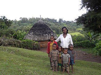 Kambaata people - Kambaata mother with her children in front of their tukul in the Kembata Tembaro Zone, Ethiopia
