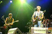 Trois hommes sur une scène, deux au premier plan derrière des pieds de microphone et jouant de la guitare et le troisième à l'arrière-plan assis derrière une batterie.