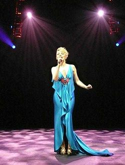 Kylie stands alone on a stage, holding a microphone near her mouth. Four spotlights shine from behind her. Her blonde hair is pulled back from her face, and she wears gold shoes and a low cut, flowing blue gown.