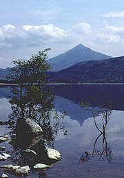 A symmetrical mountain is reflected in the waters of a lake.