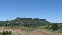 Lower Table Rock from across a field. Similar to Upper Table Rock, it rises steeply to its very flat top.