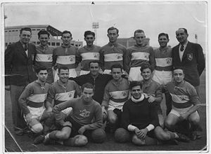 A black-and-white photograph of an association football team. A row of eight men stands at the rear, six in dark-coloured soccer jerseys with a light stripe horizontal across the centre, and one on each end in dark-coloured suits. In front of them sit eight more players. In the background a tall floodlight and two grandstands can be seen.