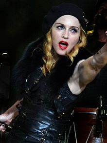 A middle-aged blond woman smiling towards the camera. She wears bright, red lipstick and a black dress with lots of straps and fur lining in it. The woman wears a cap, from which her hair comes down in waves. Her hands are near her face and she holds a microphone in her right one.