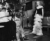 Monroe wearing a dress and facing a movie camera in a publicity photograph taken during her first film contract