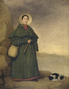 Portrait of a woman in bonnet and long dress holding rock hammer, pointing at fossil next to spaniel dog laying on ground.