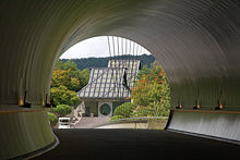 A curving circular tunnel opens to reveal a building with a tall sloping roof and a circular window in the front door.