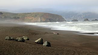 Mori Point is a prominent bluff extending into the Pacific Ocean, seen from a viewpoint looking south from Pacifica Beach.
