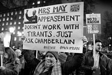 """A woman holds a sign reading """"Mrs May - appeasement doesnt work with tyrants. Just ask Chamberlain. #resist #muslimban"""
