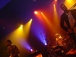 Muse tampil di Toronto, April 2004. Dari kiri ke kanan: Matthew Bellamy, Dominic Howard, dan Chris Wolstenholme.