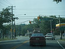 A two lane road at a traffic light in a built up area. Two traffic light poles are located on each side of the road, with a green sign on the left pole arm reading left arrow Burleigh Avenue and a green sign on the right pole arm reading Bay Shore Road County Route 603 right arrow