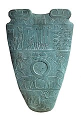 Reverse of the Narmer Palette, circa 3100 BC.  The top row depicts four men carrying standards.  Directly above them is a serekh containing the name of the king, Narmer.