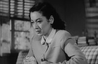 Noriko, wearing the same dress as in the Noh sequence, is shown seated on a sofa from a slightly lower angle; a window and some books are dimly visible in the background.