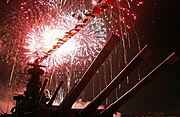 Red and yellow fireworks fill the sky, as seen from the deck of the ship. The main guns loom directly overhead.