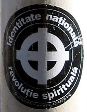 """Noua Dreaptă - A political sticker displaying the Celtic cross and the words """"identitate naţională, revoluţie spirituală"""" (national identity, spiritual revolution)."""