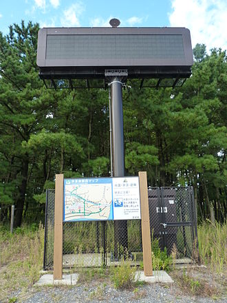Tsunami warning system - Mast with warning system, and sign detailing escape routes, on the coast of Okumatsushima, Miyagi prefecture, Japan (this coast was severely hit by the 2011 tsunami)