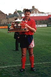 A man standing on a grass football pitch, wearing a red shirt, black shorts and red socks, and holding a trophy.