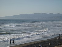 Two people on the shore of the Pacific Ocean
