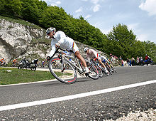 A group of cyclists, in a single-file line, on a road that is descending in elevation. The cyclist in the front of the group wears a white rain jacket, and his shorts bear rainbow stripes.