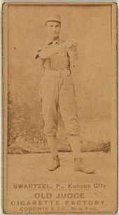 A baseball player is standing in his uniform, holding a baseball.