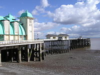 A pier beneath a cloudy sky, with a large white and green building and some smaller huts on it