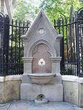 "A Gothic drinking fountain and metal railings, with a park visible at an elevated level through the railings. An inscription on the drinking fountain reads ""James & Mary Ann Ward late of Aldersgate and Islington Erected by their daughters 1876""."