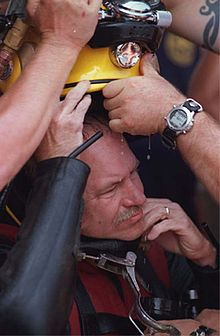 A diver being helped out of his bulky diving gear