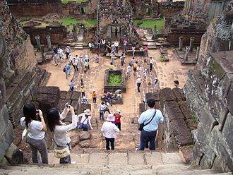 Cultural tourism - Tourists taking pictures at the khmer Pre Rup temple ruins, an example of cultural tourism.