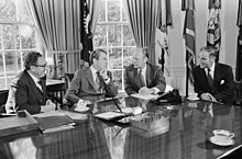 President Richard Nixon seated at his Oval Office desk during a meeting with Henry Kissinger, Alexander Haig, and Gerald Ford.jpg
