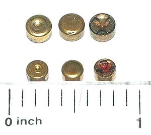 Centerfire ammunition - Large (top row) and small (bottom row) pistol cartridge Boxer primers. (L–R fired, unfired, and inside view.) The tri-lobe object inside the primer is the anvil.