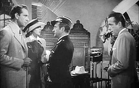 Black-and-white film screenshot of several people in a nightclub. A man on the far left is wearing a suit and has a woman standing next to him wearing a hat and dress. A man at the center is looking at the man on the left. A man on the far right is wearing a suit and looking to the other people.