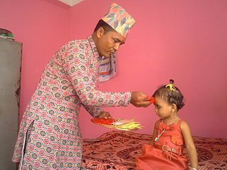 Dashain - Elder celebrating Dashain festival by putting tika on a child