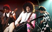 Colour photograph of John Deacon, Brian May and Freddie Mercury of Queen performing live in 1978.