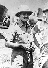 Portrait of a man in tropical military uniform. He is wearing a bucket hat, and military aircraft can be seen in the background.